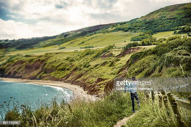 boy taking images of coastal scenery - yorkshire england stock pictures, royalty-free photos & images