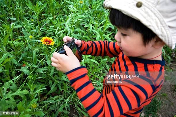 Boy taking photo of flower