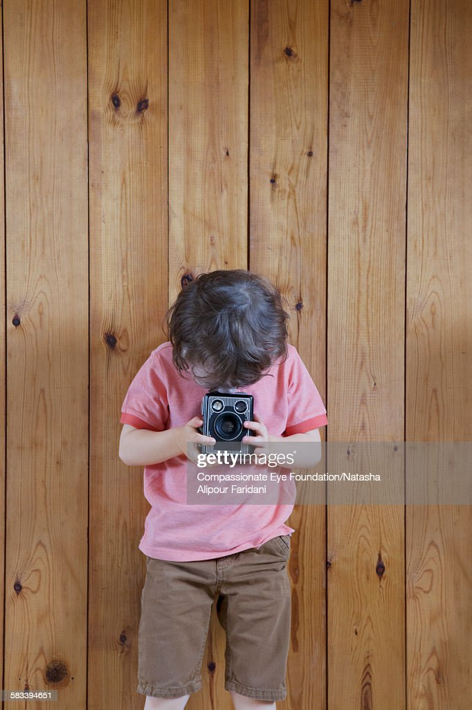 Boy taking photo with vintage camera : Stock Photo