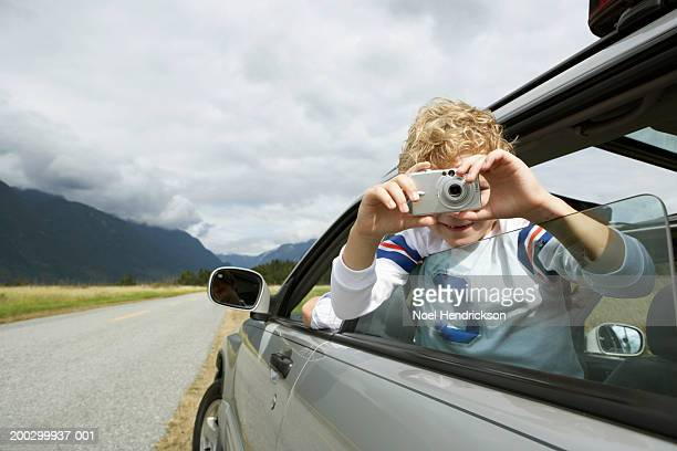 Boy (5-7 years) taking photograph from car window, smiling, portrait, close-up