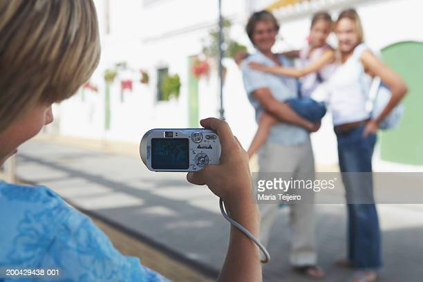 Boy (8-10) taking photograph of family (focus on camera)