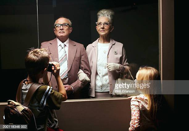 boy (8-10) taking photograph of senior couple behind glass partition - beehive hair stock photos and pictures