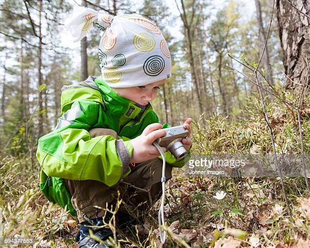 Boy taking picture in forest