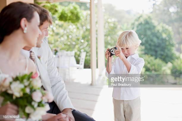 Junge nimmt ein Bild von Braut und Bräutigam