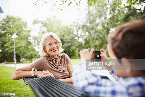 Boy taking picture of grandmother on park bench