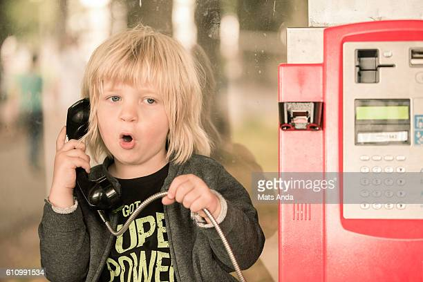Boy talking in a pay phone