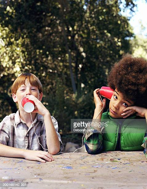 Boy (8-10) talking into cup attached to string, friend listening
