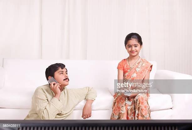 boy talking on mobile phone while girl watches tv - mangala sutra fotografías e imágenes de stock