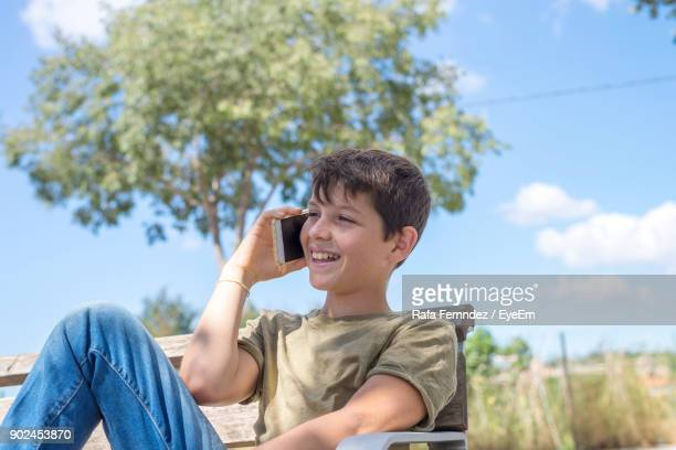 Boy Talking On Mobile Phone While Sitting On Bench Against Sky