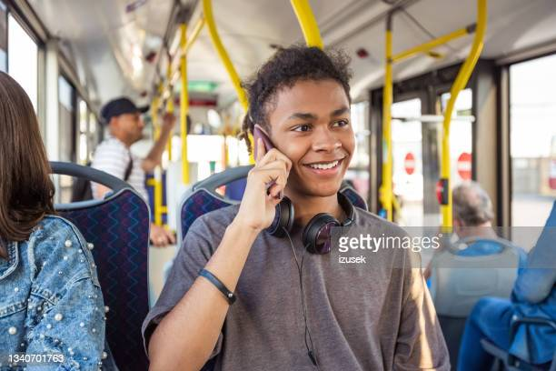 boy talking on mobile phone while traveling in bus - izusek stock pictures, royalty-free photos & images