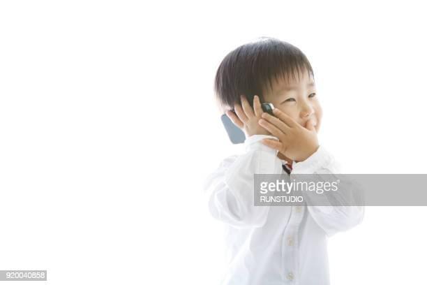 boy talking on smartphone - 男の子一人 ストックフォトと画像