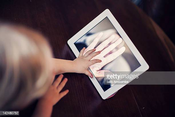 Boy talking to his mummy over internet on tablet