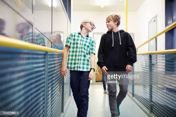 boy talking with male friend while walking in school corridor - 10歳から11歳 ストックフォトと画像
