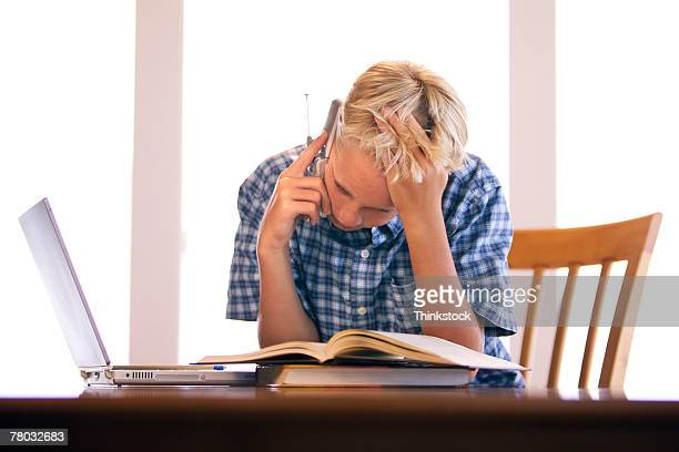 A boy talks on his cell phone while leaning over his homework books and laptop