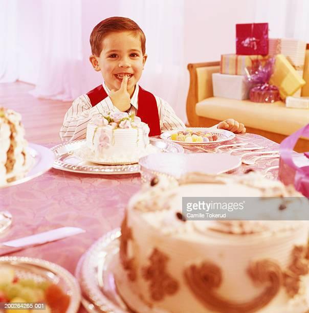 boy (3-5) tasting cake at party - happy birthday vintage stockfoto's en -beelden