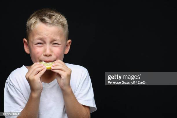 boy tasting lemon against black background - one boy only stock pictures, royalty-free photos & images