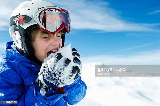 Boy tasting snowball on mountain