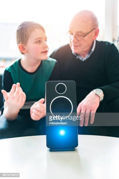Boy teaches grandparent about how to use a digital asstant using your voice
