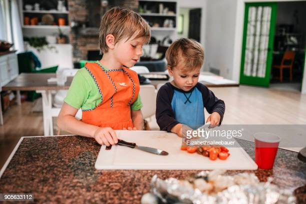 Boy teaching his brother how to chop tomatoes