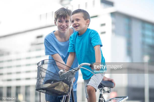 Boy teaching little brother how to ride a bycicle