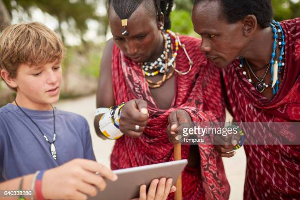 Boy teaching Maasai warriors to use a digital tablet.