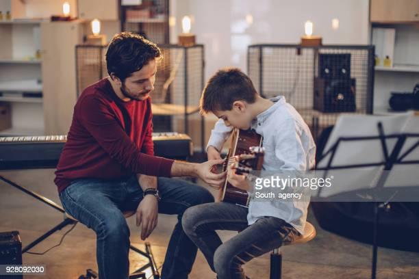 rapaz ensinando a tocar guitarra na escola de música - música - fotografias e filmes do acervo