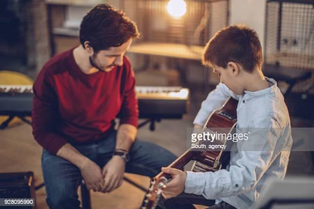 Boy teaching to play guitar