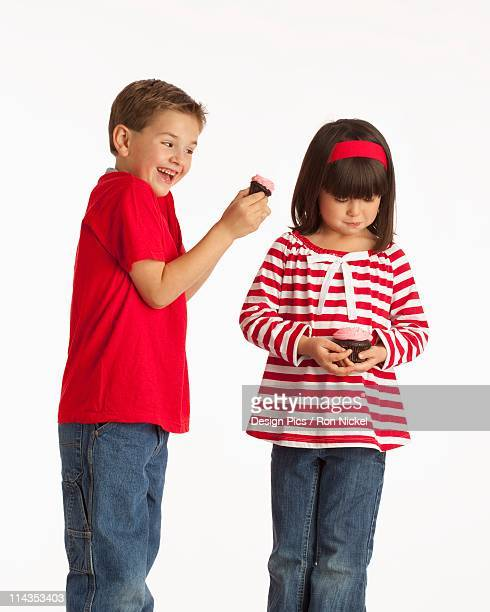 A Boy Teasing A Girl With His Chocolate Cupcake