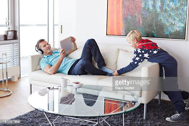 boy teasing his father while using tablet - tickling feet stock photos and pictures