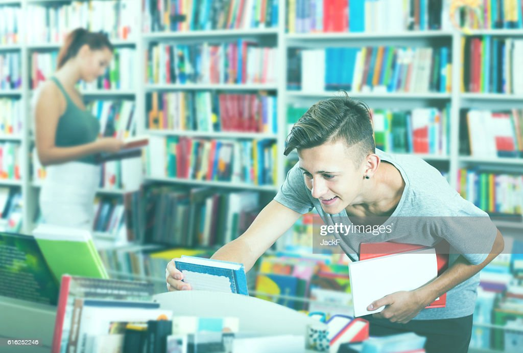 Boy teenager choosing new book in shop : Foto de stock