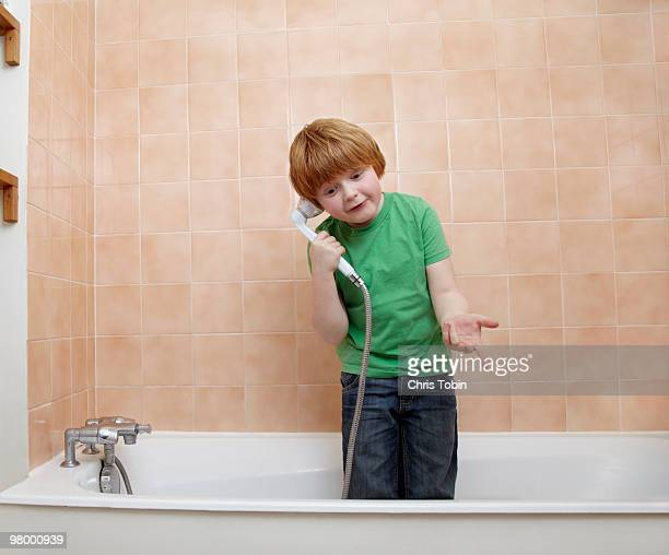 boy telephoning with showerhead in bathtub