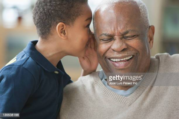 Boy telling grandfather a secret