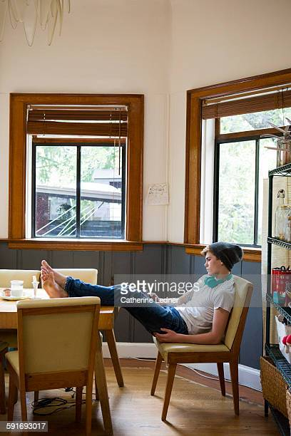 boy texting at kitchen table with feet up - teen boy barefoot stock photos and pictures