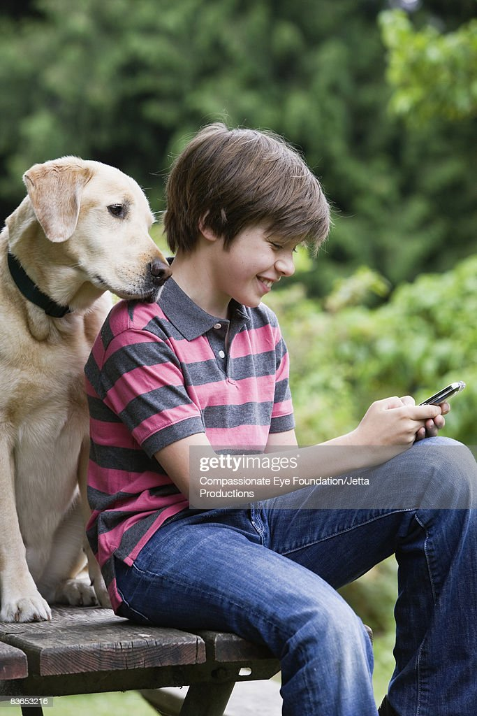 Boy texting, dog looking over shoulder : Stock Photo