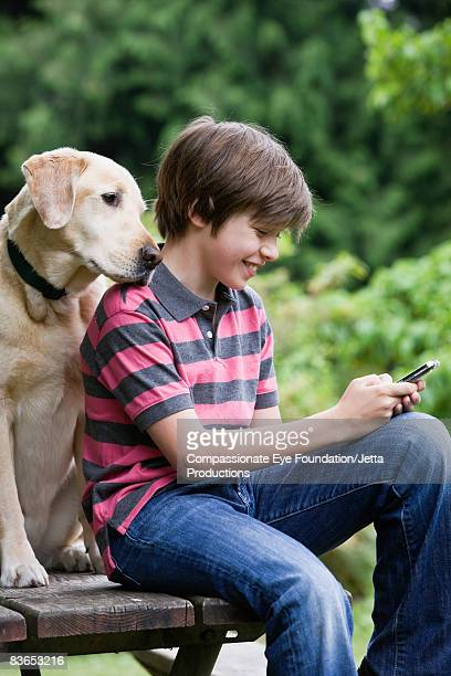 Boy texting, dog looking over shoulder