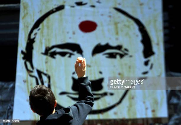 A boy thows an egg at an image of Russian President Vladimir Putin depicted as late German Nazi dictator Adolf Hitler during a flash mob event in the...