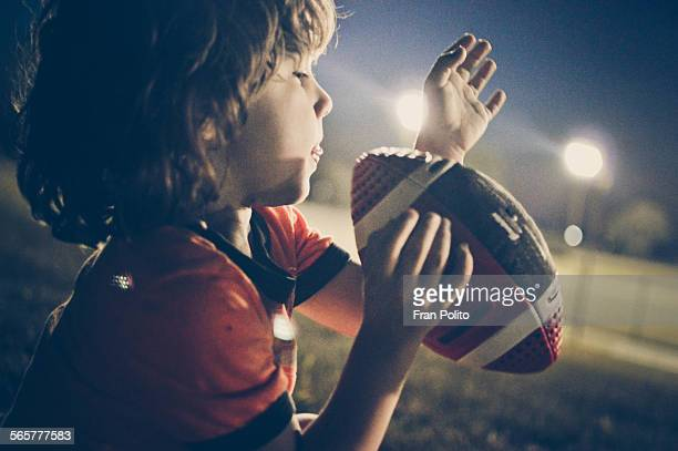 Boy throwing a football at night.