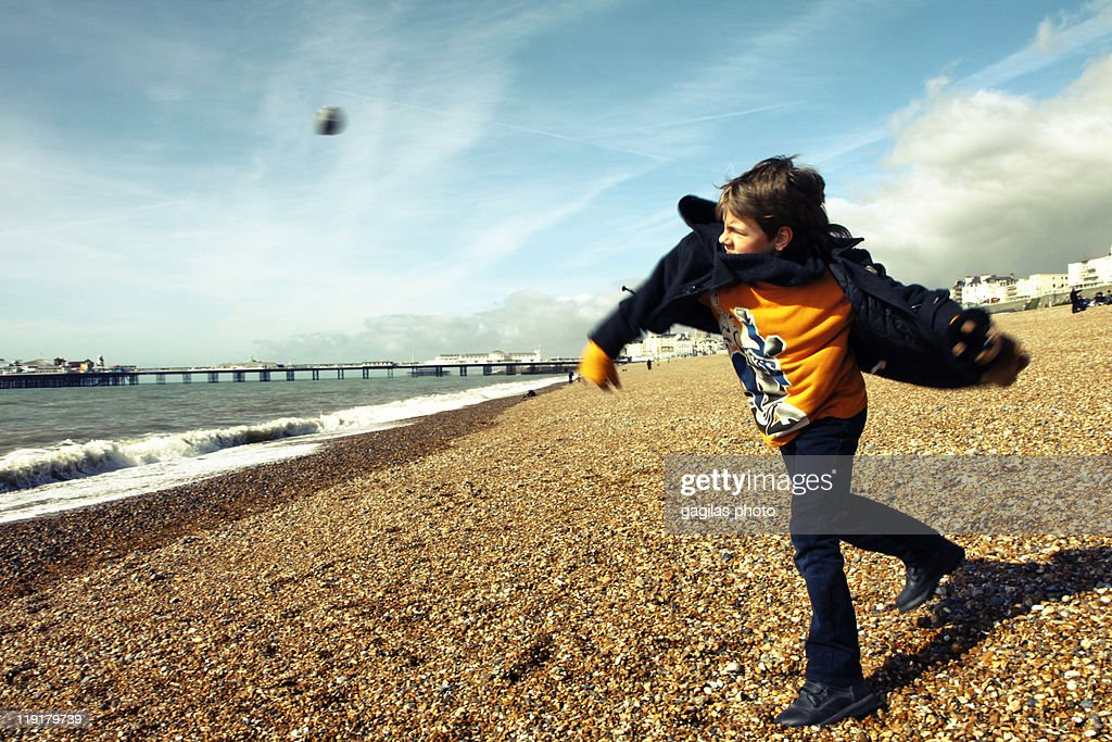 Boy throwing away stone on beach : Stock Photo