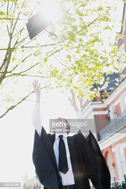 Boy throwing mortarboard overhead
