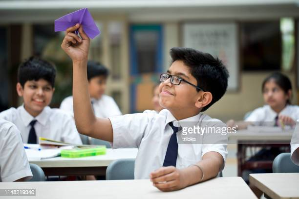 boy throwing paper airplane in classroom - asian boy stock pictures, royalty-free photos & images