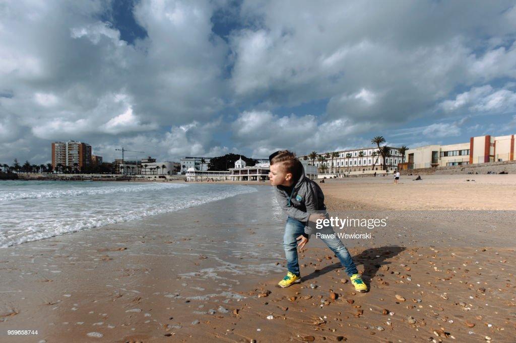 Boy throwing rocks into sea : Stock-Foto