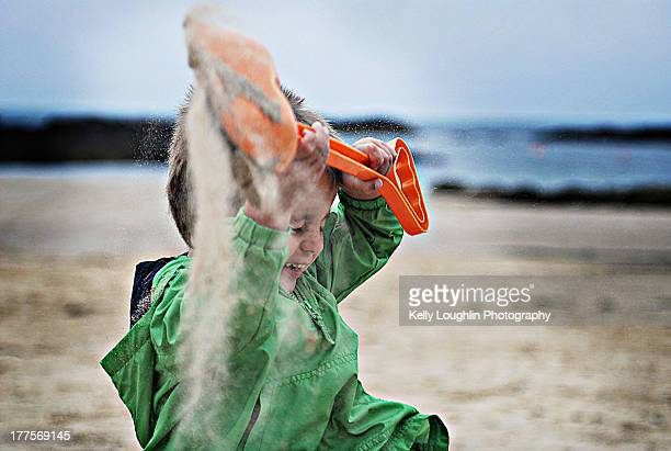Boy Throwing Sand on Beach in Ireland