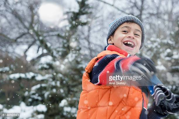 Boy throwing snowball outdoors