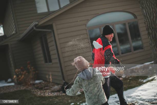 boy throwing snowballs at father - sioux falls stock pictures, royalty-free photos & images