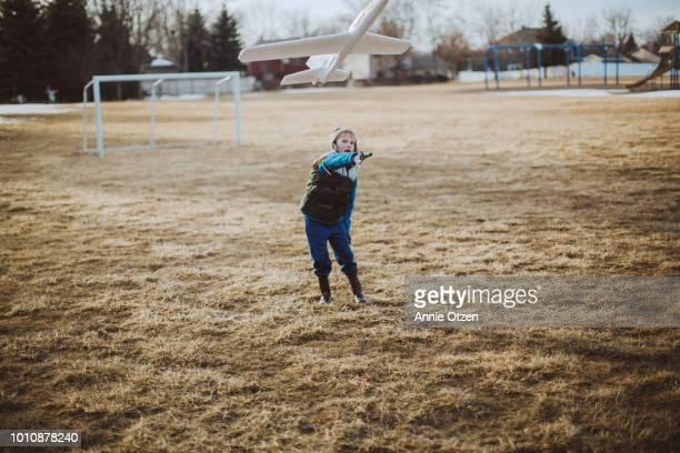 Boy Throwing Toy Airplane
