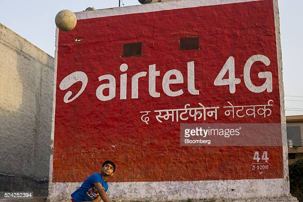 A boy throws a ball in front of a painted advertisement for Bharti Airtel Ltd displayed on the side of a building in Murthal Haryana India on Friday...