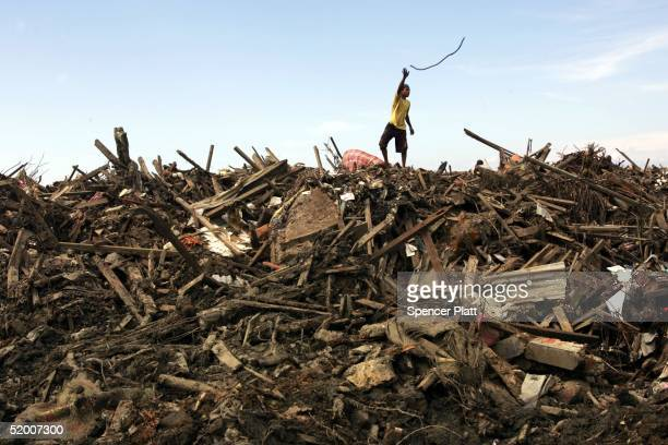 A boy throws a piece of wire scavenged in the remains of tsunami damaged homes January 18 2005 in Banda Aceh Indonesia Thousands of residents are...