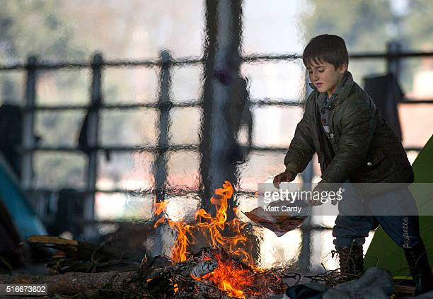 A boy throws paper onto a fire lit between tents erected inside an old railway shed where people are sheltering at the Idomeni refugee camp on the...