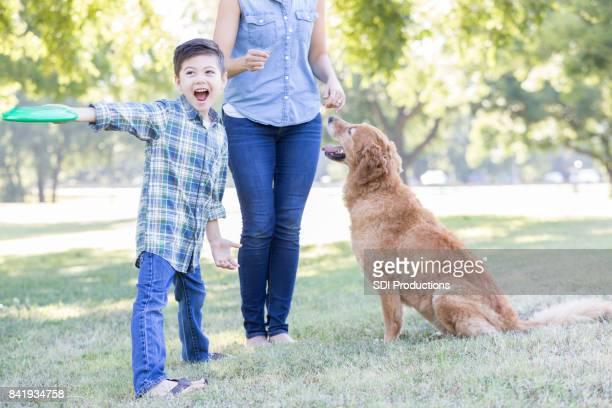 少年は犬にプラスチック製のディスクをスローします。 - training grounds ストックフォトと画像