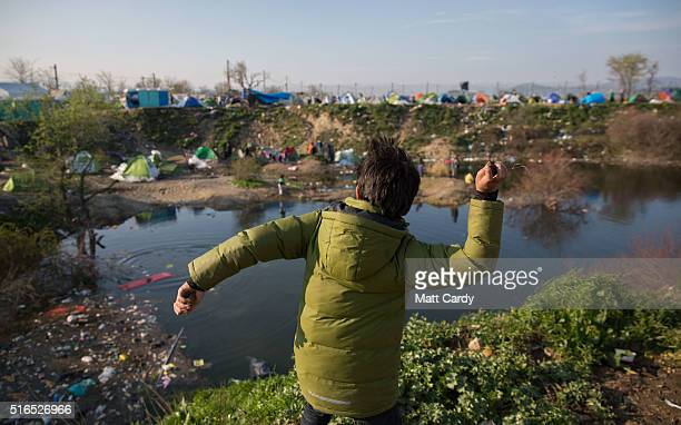 A boy throws stones into a lake of rain water at the Idomeni refugee camp on the Greek Macedonia border on March 19 2016 in Idomeni Greece Thousands...